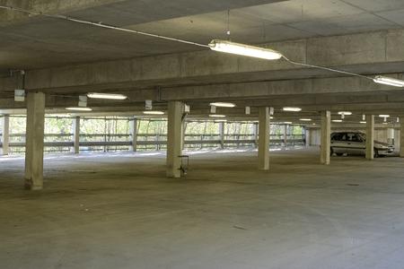 tubos fluorescentes: Iluminado por el resplandor enfermizo de tubos fluorescentes baratas, un aparcamiento subterráneo se encuentra casi vacío, un coche se deja. Editorial