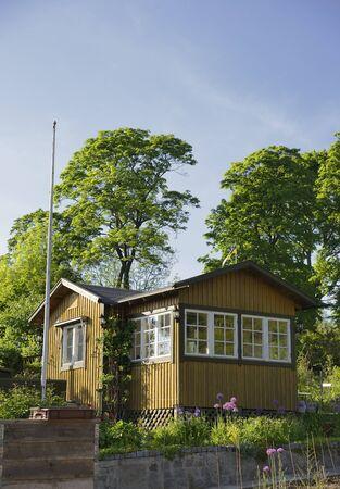 idyllic: Idyllic yellow cottage in botanical garden Stock Photo