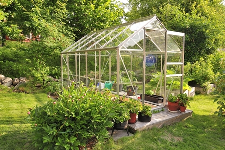 A garden center greenhouse with a colorful display of potted plants and flowers Stock Photo