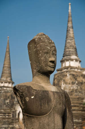 Stupa (chedi) of a Wat in Ayutthaya, Thailand, with Buddha staue. Ayutthaya city is the capital of Ayutthaya province in Thailand. Its historical park is a UNESCO world heritage. photo