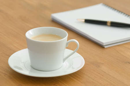 stock listing: White coffee cup with open book on a wooden table