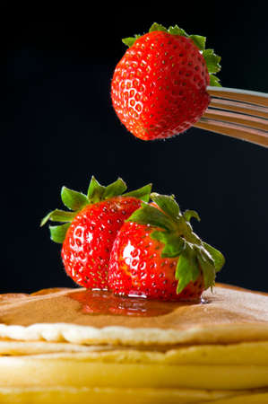 hotcakes: Strawberry butter pancake with honey maple sirup flowing down closeup shoot, one strawberry lifting up