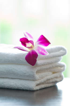 Spa towels and orchid flowers in front of a white background Stock Photo
