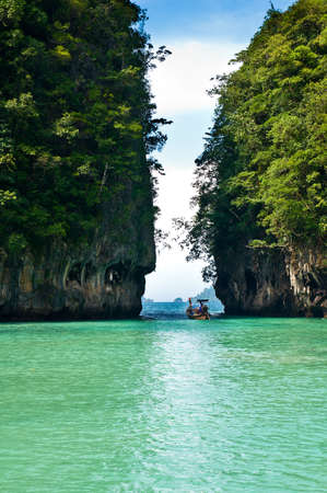 Turquoise lagoon in Thailand with a boat in the background photo