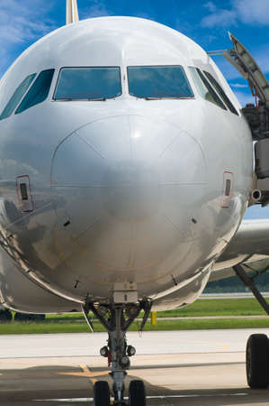 Closeup of airplane nose with pilot cabin against blue sky, selective focus photo
