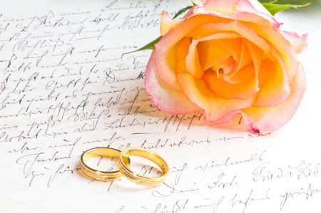 Rose, rings over handwritten love letter photo