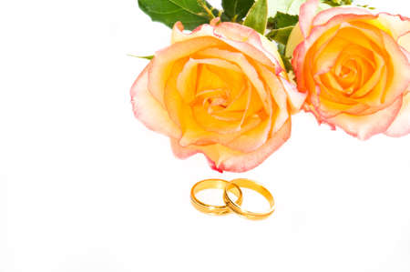 Red yellow roses and golden wedding ring over white photo