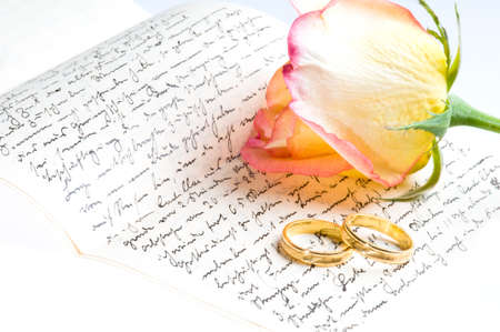 Red yellow rose, gold ring over a hand written love letter photo
