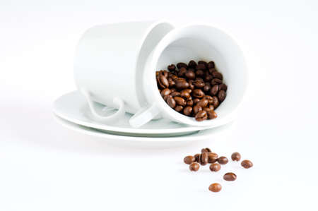 Coffee cups and coffee beans over white photo