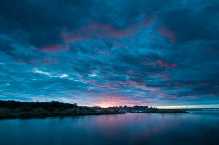 Sunset over a river with burning clouds Stock Photo - 8810691