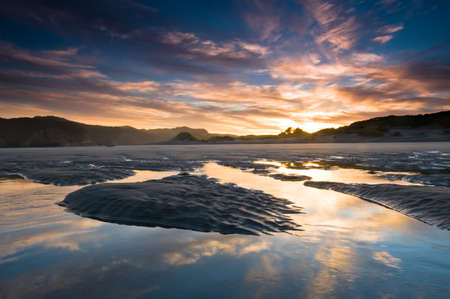 Sunrise above beach with reflection on incoming tide Stock Photo - 8902421