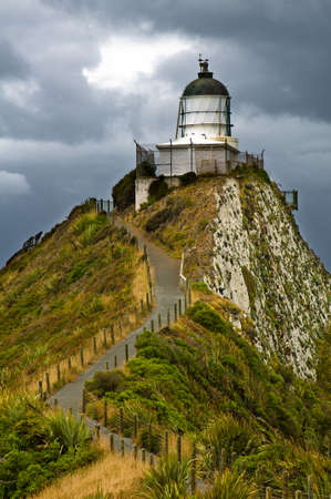 Nugget Point Light House an dark clouds in the sky, Catlins, New Zealand photo