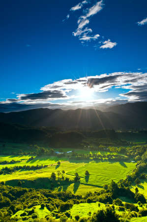 Sunrays flood farmland during sunset in amazing light Stock Photo - 8995057