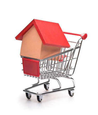 Shopping cart with red roofed house over white Stock Photo