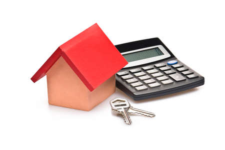 red roofed house over white with calculator and house keys photo