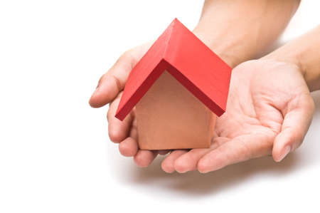 roofed house: red roofed house over white in human hand