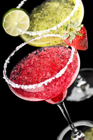 garnish: One Classic and a Strawberry Margarita in front of a black background with fresh garnish