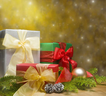 Three presents decorated with gold satin and Christmas decoration, with space for advertising text photo