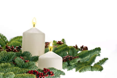 Two candles in advent setting with real Christmas tree branches photo