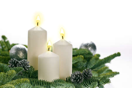 Three candles in advent setting with real Christmas tree branches