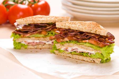 mayonesa: Dos sandwich en envoltura de segundo plano de papel tiene tomates y vajilla Foto de archivo