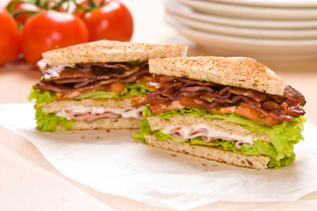 ham sandwich: Two sandwich on wrapping paper back ground has tomatoes and dishware