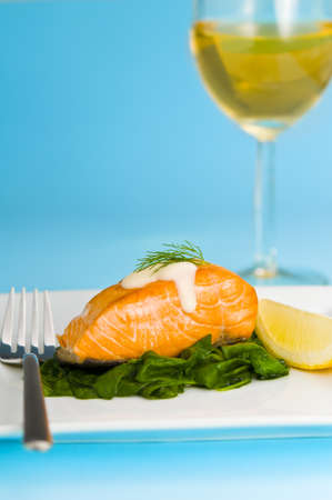 wine sauce: Salmon steak on spinach, decorated with lemon, sauce and fork