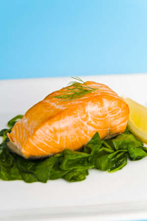 salmon dinner: Salmon steak on spinach, decorated with lemon and dill