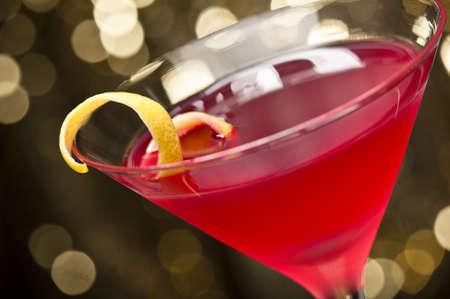 coctel de frutas: C�ctel Cosmopolitan con guarnici�n de lim�n en delante de un fondo brillo del oro