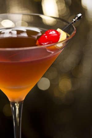bebidas alcoh�licas: C�ctel Manhattan adornado con una baja de nuevo brillo cereza y el lim�n y el oro Foto de archivo