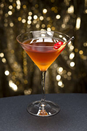 Manhattan cocktail garnished with a cherry and lemon and gold glitter back ground photo