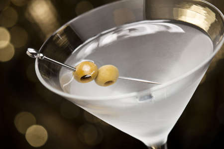 dry food: Vodka Martini with olive garnish in front of a gold glitter background