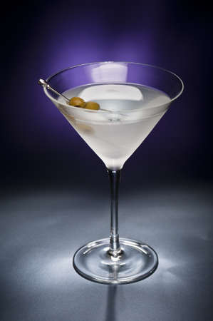 Vodka Martini with olive garnish in front of a black blue background photo