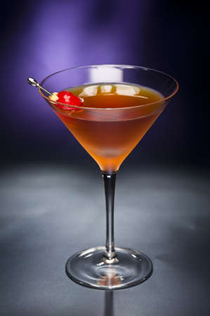Manhattan cocktail garnished with a cherry and lemon with blue black back ground Stock Photo