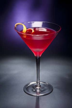 Cosmopolitan cocktail with lemon garnish in front of a black blue background photo