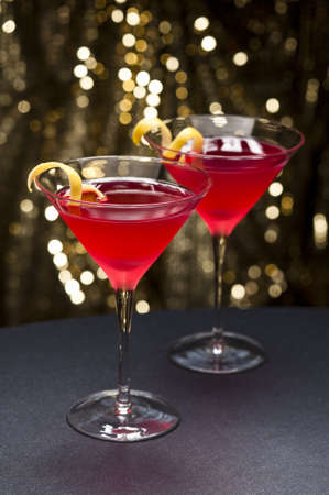 Cosmopolitan cocktail with lemon garnish in front of a gold glitter background Stock Photo - 11260822