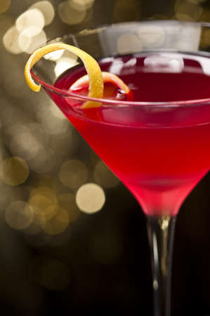 Cosmopolitan cocktail with lemon garnish in front of a gold glitter background photo