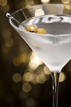 copa de martini: Vodka Martini, con guarnici�n de oliva frente a un fondo de brillo del oro