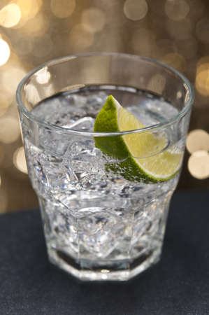gin: Gin Tonic Cocktail in front of a brown gold background