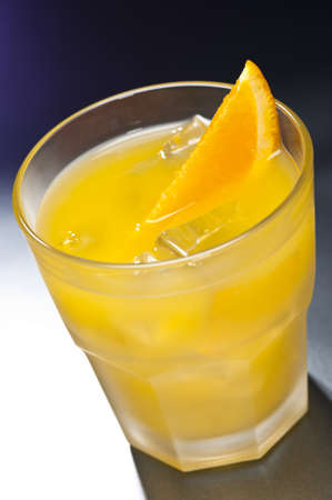 alcohol screwdriver: Screwdriver cocktail in front of different colored backgrounds Stock Photo