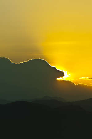Sunset behind mountains with golden color photo