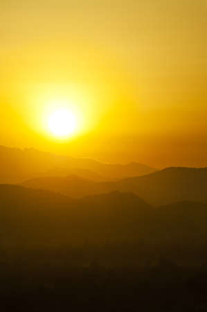 Sunset behind mountains with golden color Stock Photo