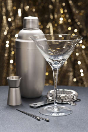 One Martini glass with bartender tools in front of a glitter background photo