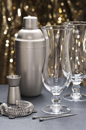 Two Highball glass with bartender tools in front of gold glitter background Stock Photo - 12233071