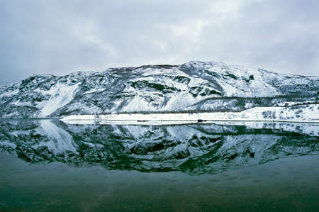 arctic landscape: The Mountain reflection in a Fjord in Norway above the arctic circle in Winter