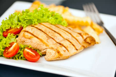 chicken breast: Chicken, French fries and salad in a nice setting