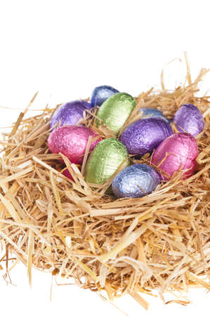 Straw nest with chocolate Easter eggs over white studio shoot photo