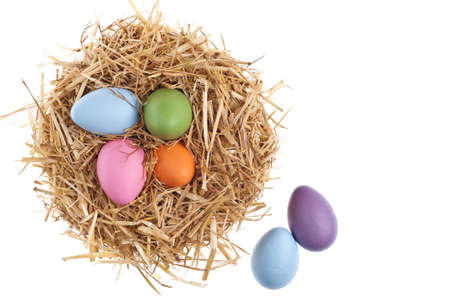 Straw nest with nice colored Easter eggs over white studio shoot photo