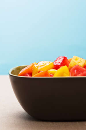 One bowl of Mixed tropical fruit salad in front of blue background Stock Photo - 12917429