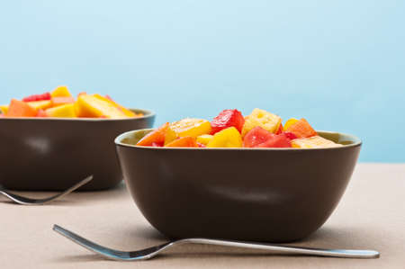 Two bowl of Mixed tropical fruit salad in front of blue background photo